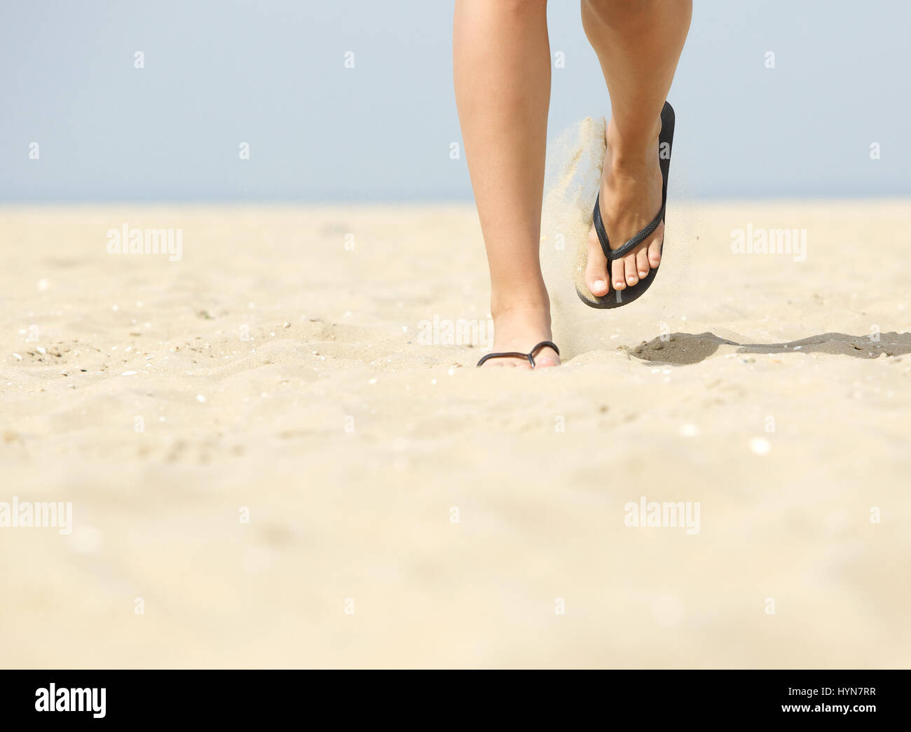 6b068fb271b613 Low angle view of woman feet walking forward in flip flops on beach ...