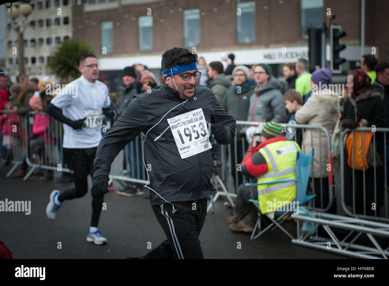 Tired and exhausted runners cross the finish line during the Worthing Half Marathon in Worthing, West Sussex, UK. - Stock Image