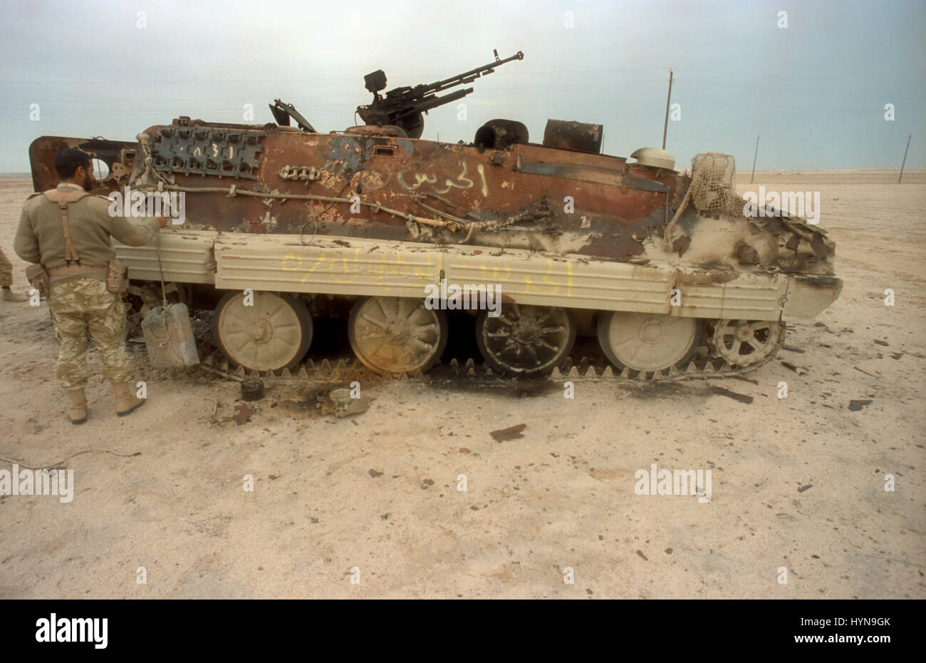 A Qatari soldier inspects an Iraqi armored personnel carrier destroyed by U.S Aircraft following the Battle of Khafji - Stock Image