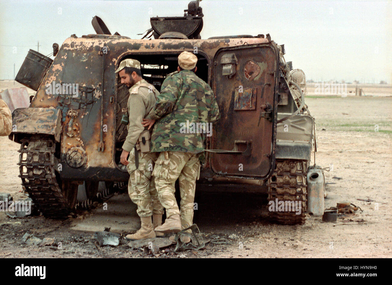 A Qatari soldiers inspect an Iraqi armored personnel carrier destroyed by U.S Aircraft following the Battle of Khafji - Stock Image