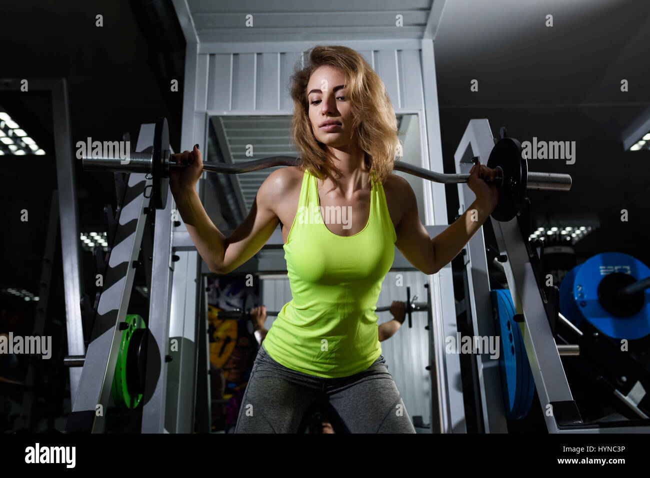 Girl in gym with barbell - Stock Image