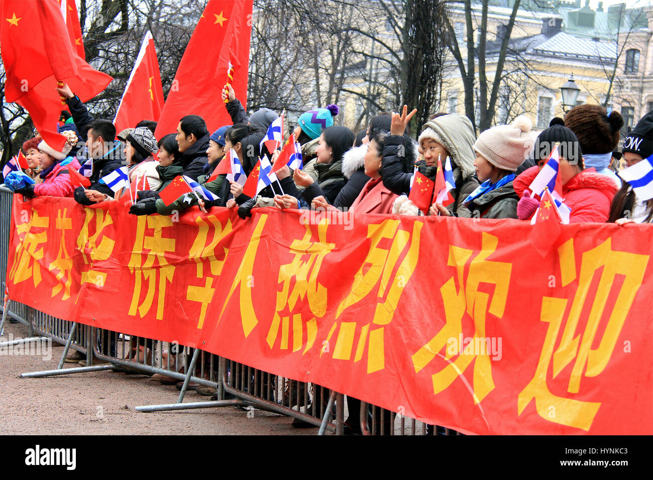 HELSINKI, FINLAND - APRIL 5, 2017: Chinese people wave Finnish and Chinese flags as they wait to see President Xi - Stock Image