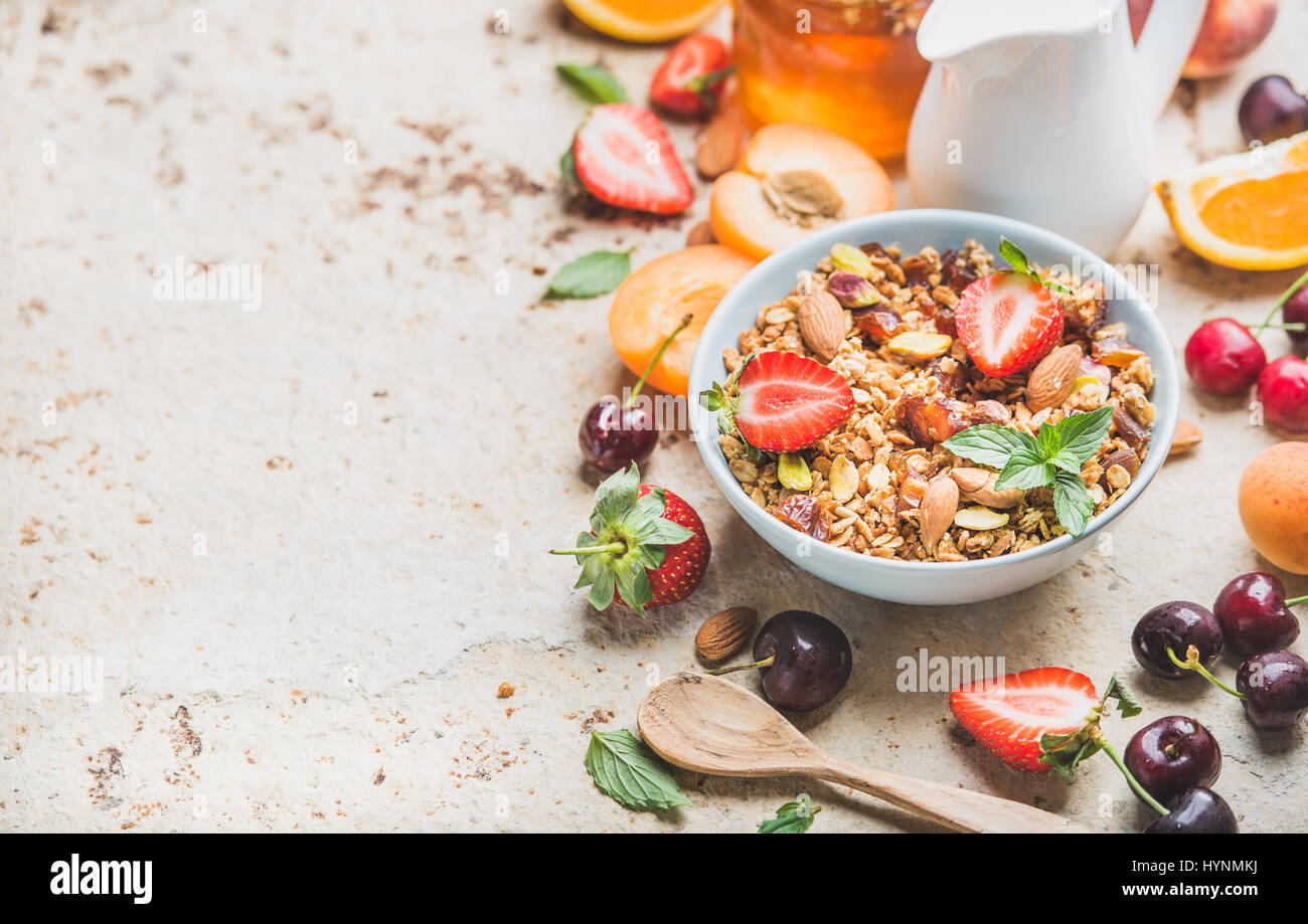 Healthy breakfast ingredients. Bowl of oat granola with milk, fresh fruit, berries and honey - Stock Image