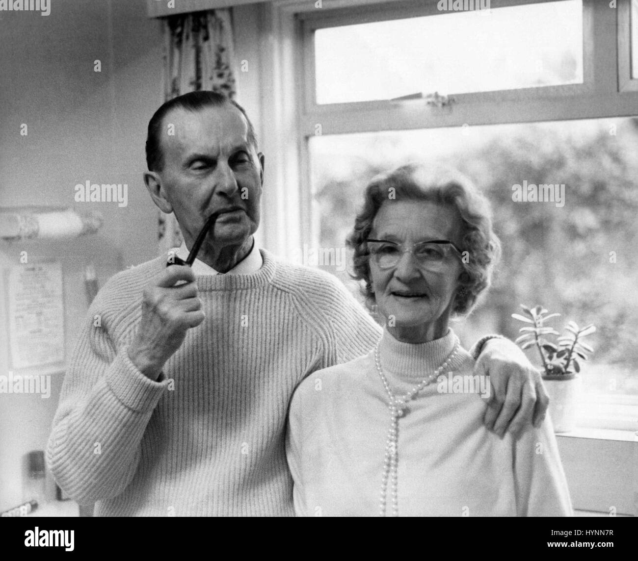 An elderly married couple in their eighties pose in the kitchen of their home at Bembridge, Isle of Wight on December - Stock Image