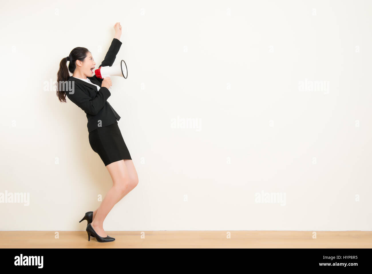 business woman talking in megaphone with white wall background. beautiful asian office lady. face expression emotion Stock Photo