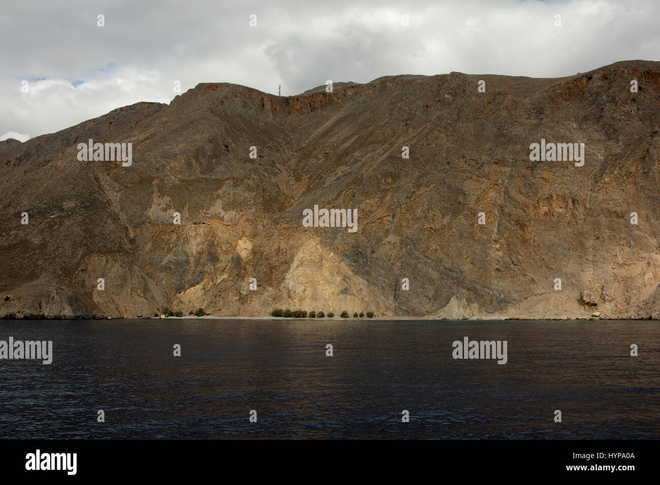 Sweet water beach under the bare mountains at Crete's south coast.  . Stock Photo
