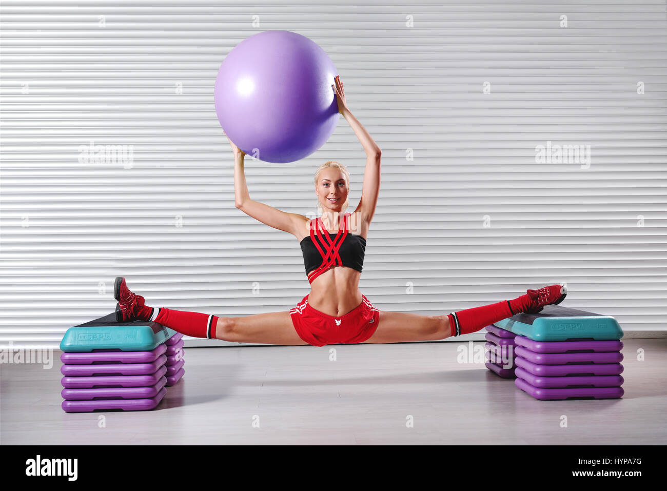 Beautiful young flexible fitness woman doing splits during her w - Stock Image