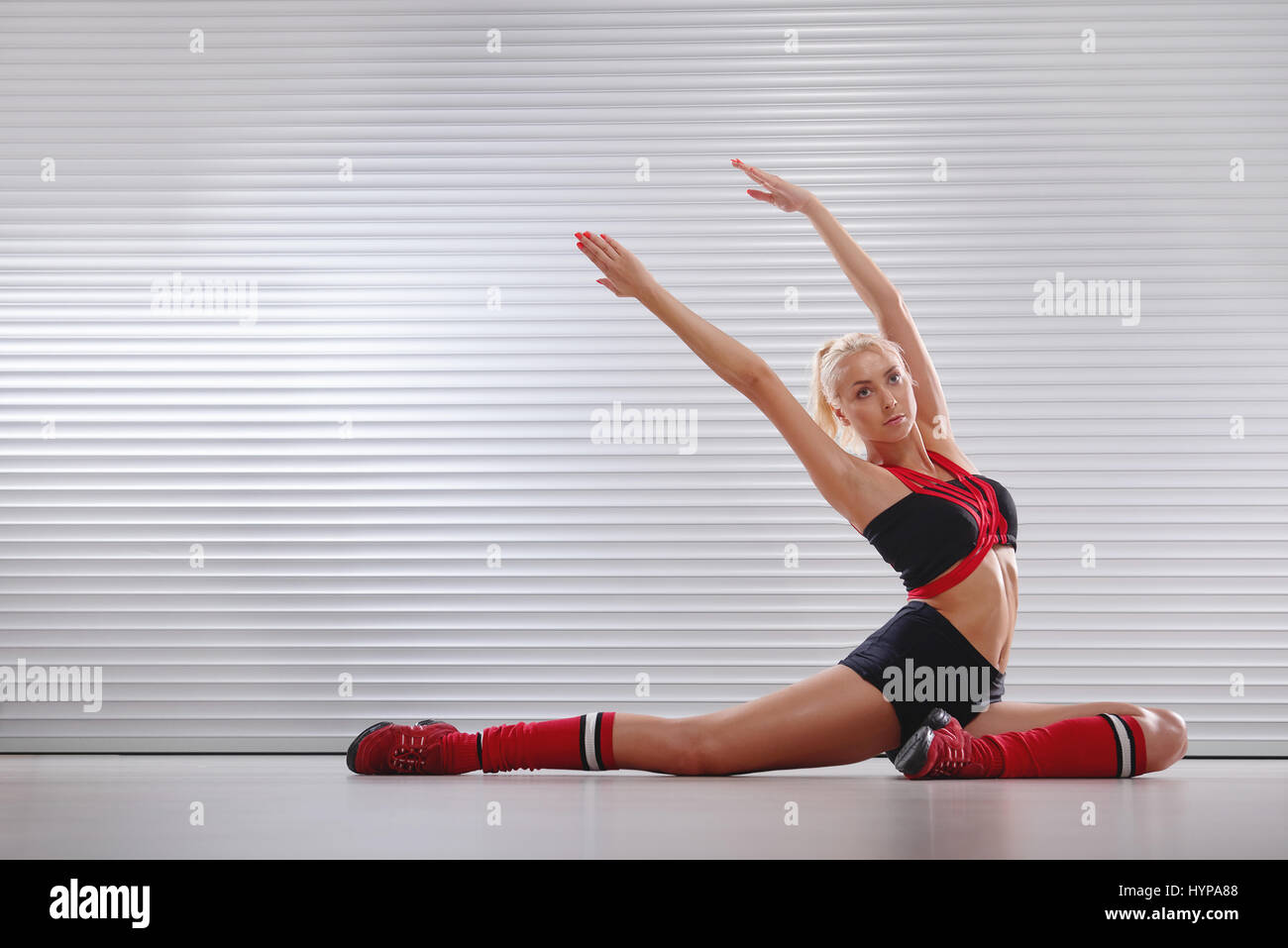 Beautiful athletic young female stretching before her workout  - Stock Image