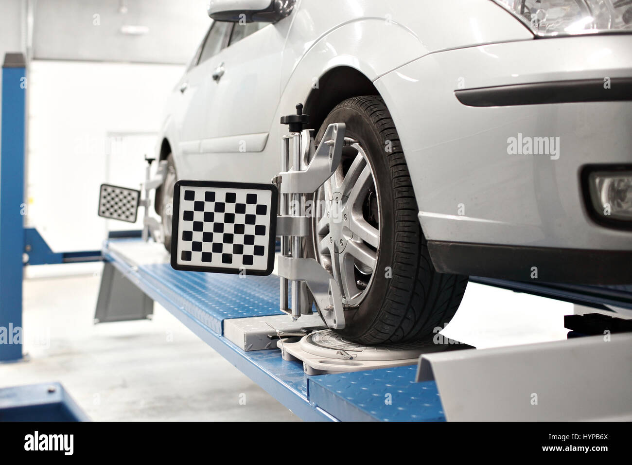 Grid sensor sets mechanic on auto. Car stand with sensors wheels for alignment camber check in workshop of Service - Stock Image