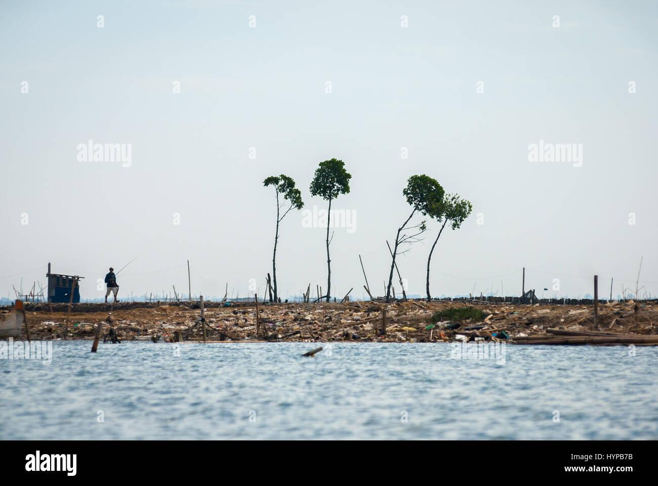 A man walking in the dry coastal land in North Jakarta, Jakarta, Indonesia. © Reynold Sumayku - Stock Image