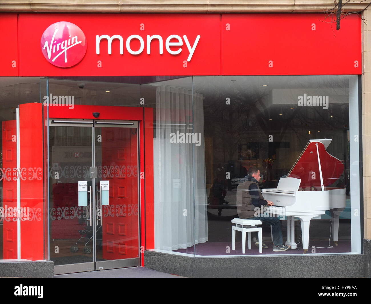 A customer of a Virgin Money bank in Sheffield sits in the window playing a white grand piano - other gimmicks at - Stock Image