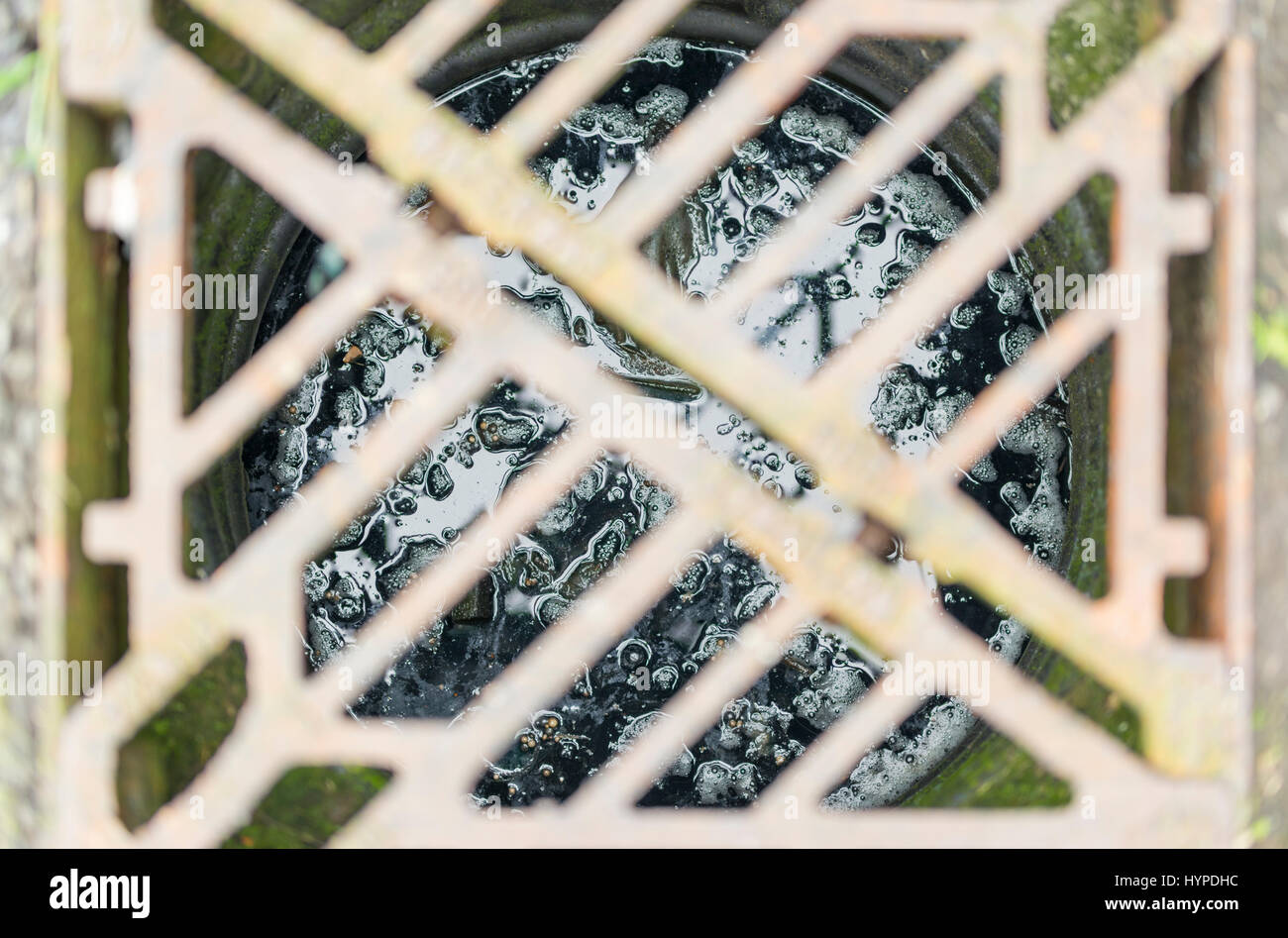 View looking down into a storm drain, with the grating out of focus, and showing wet sludge at the bottom of the - Stock Image