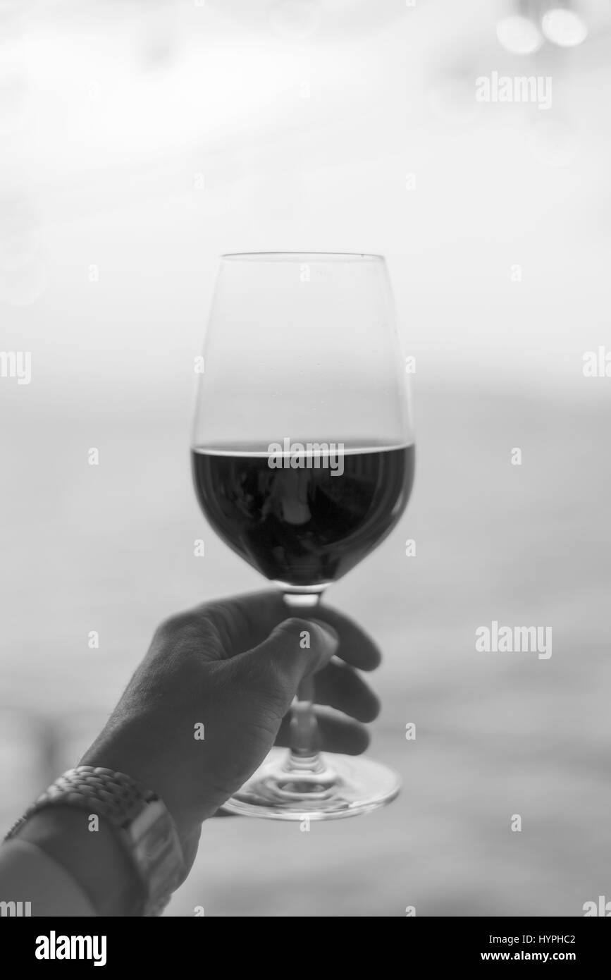 Vertical portrait black and white man holding red wine glass up - Stock Image