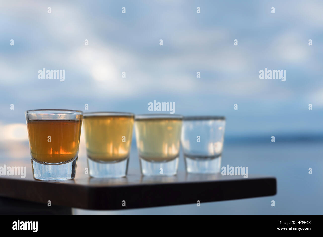 Four shots of a variety of tequila on seaside table - Stock Image