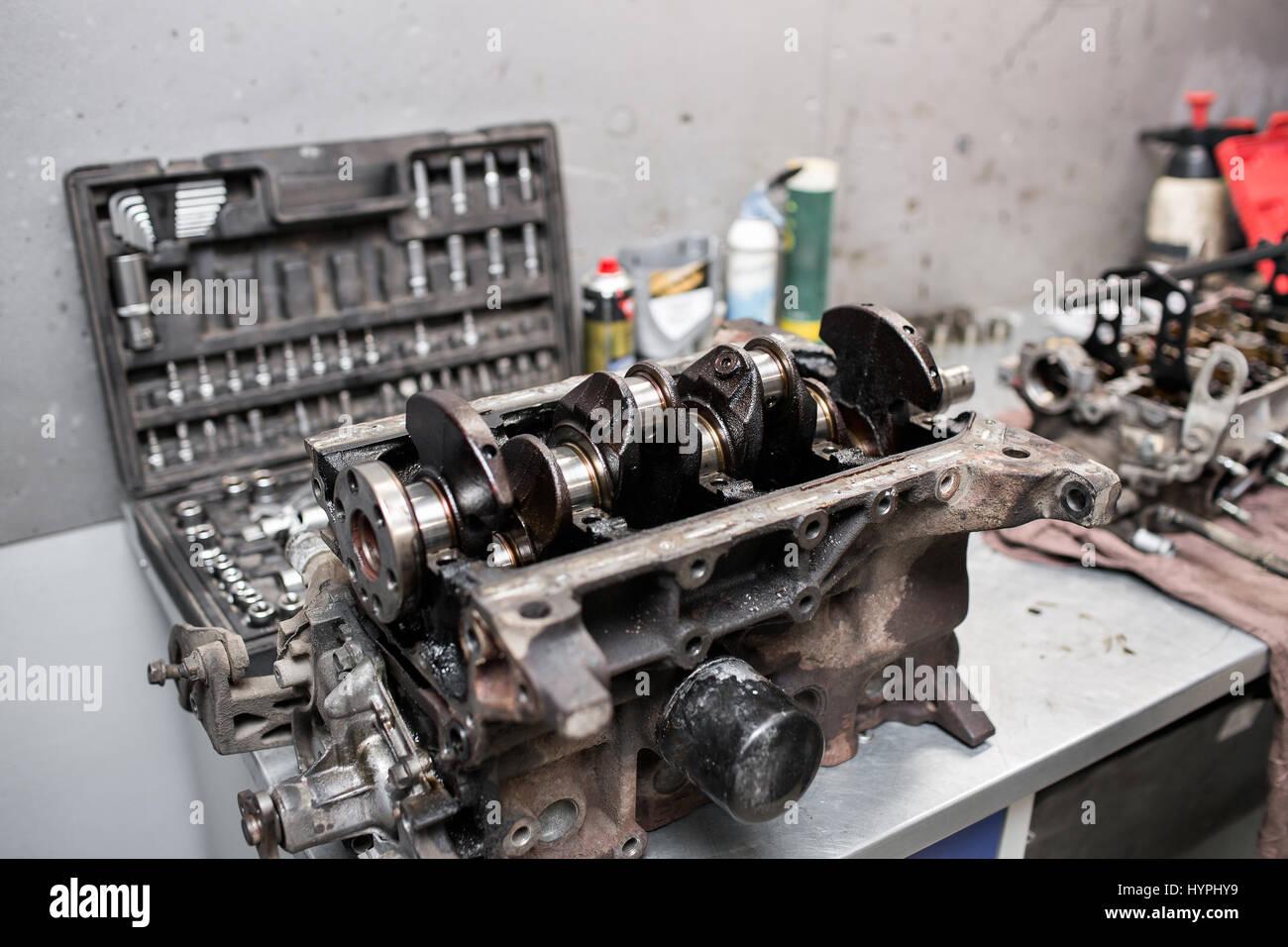 Engine crankshaft, valve cover, pistons. mechanic repairman at automobile car engine maintenance repair work - Stock Image
