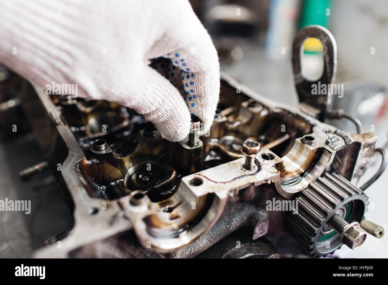 Engine crankshaft, valve cover, pistons. mechanic repairman at automobile car engine maintenance repair work - Stock Image