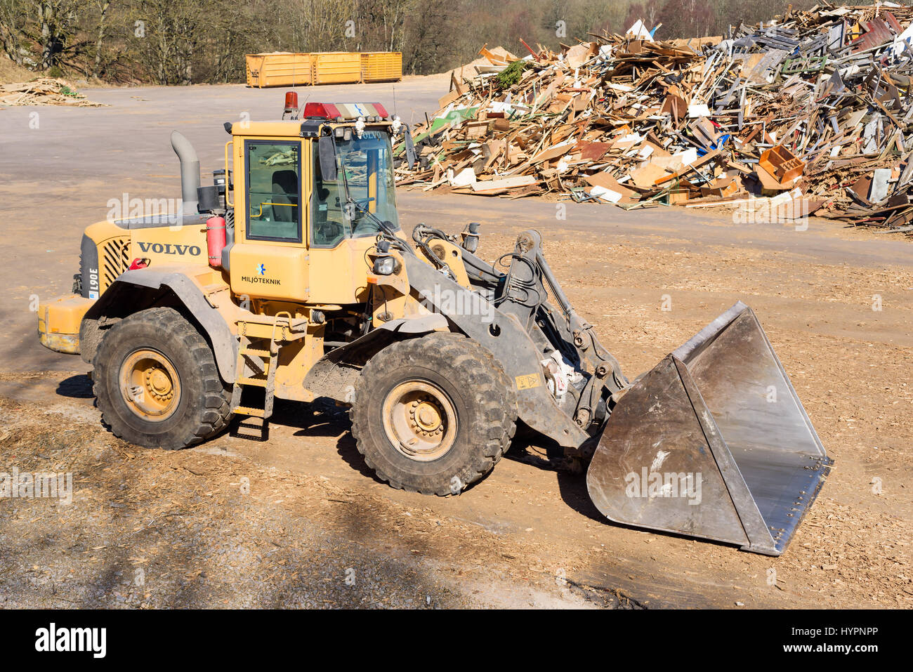 Ronneby, Sweden - March 27, 2017: Documentary of public waste station. Volvo L90e wheel loader parked with pile - Stock Image