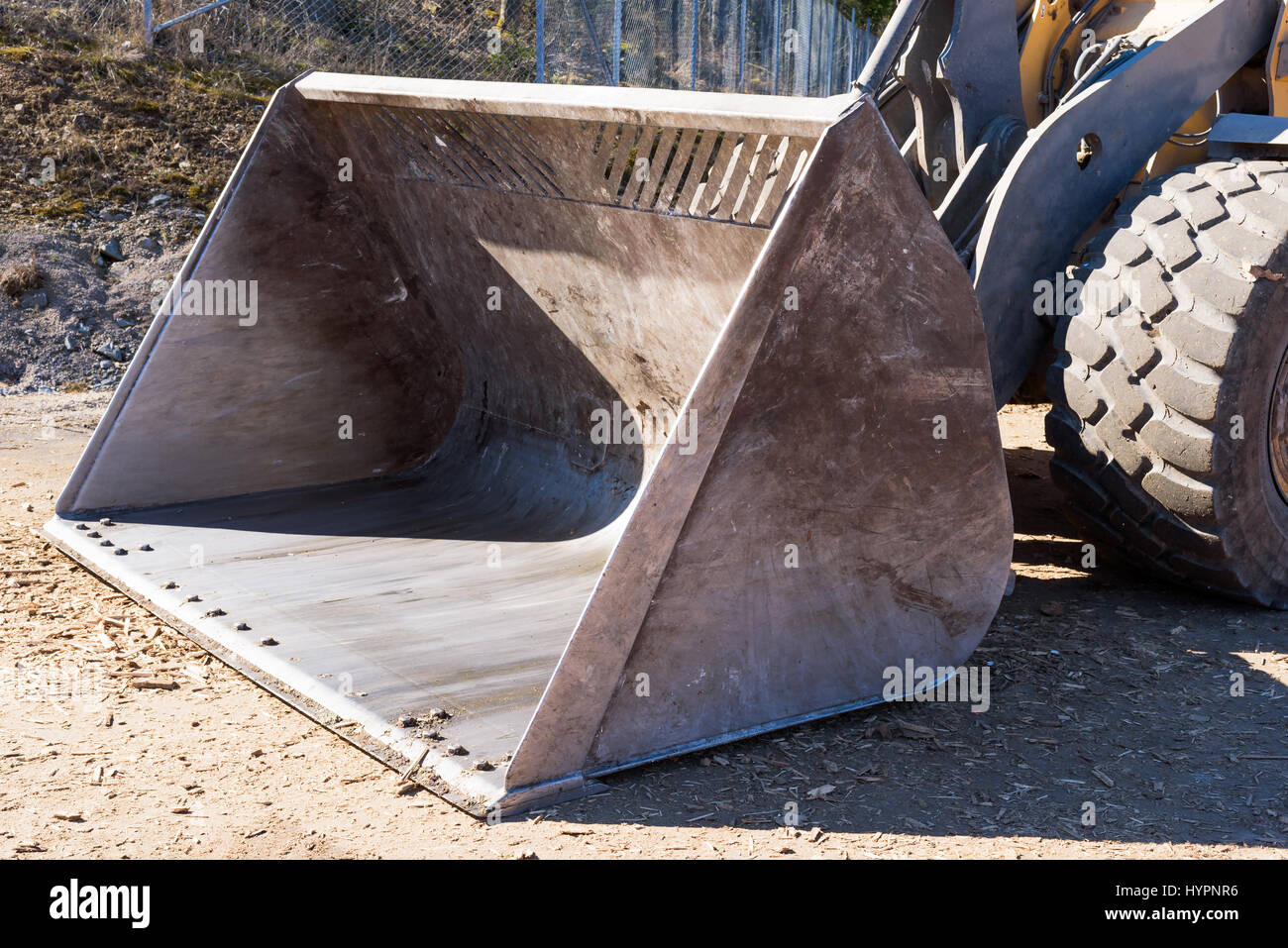 Front loader bucket seen from the side and front. - Stock Image