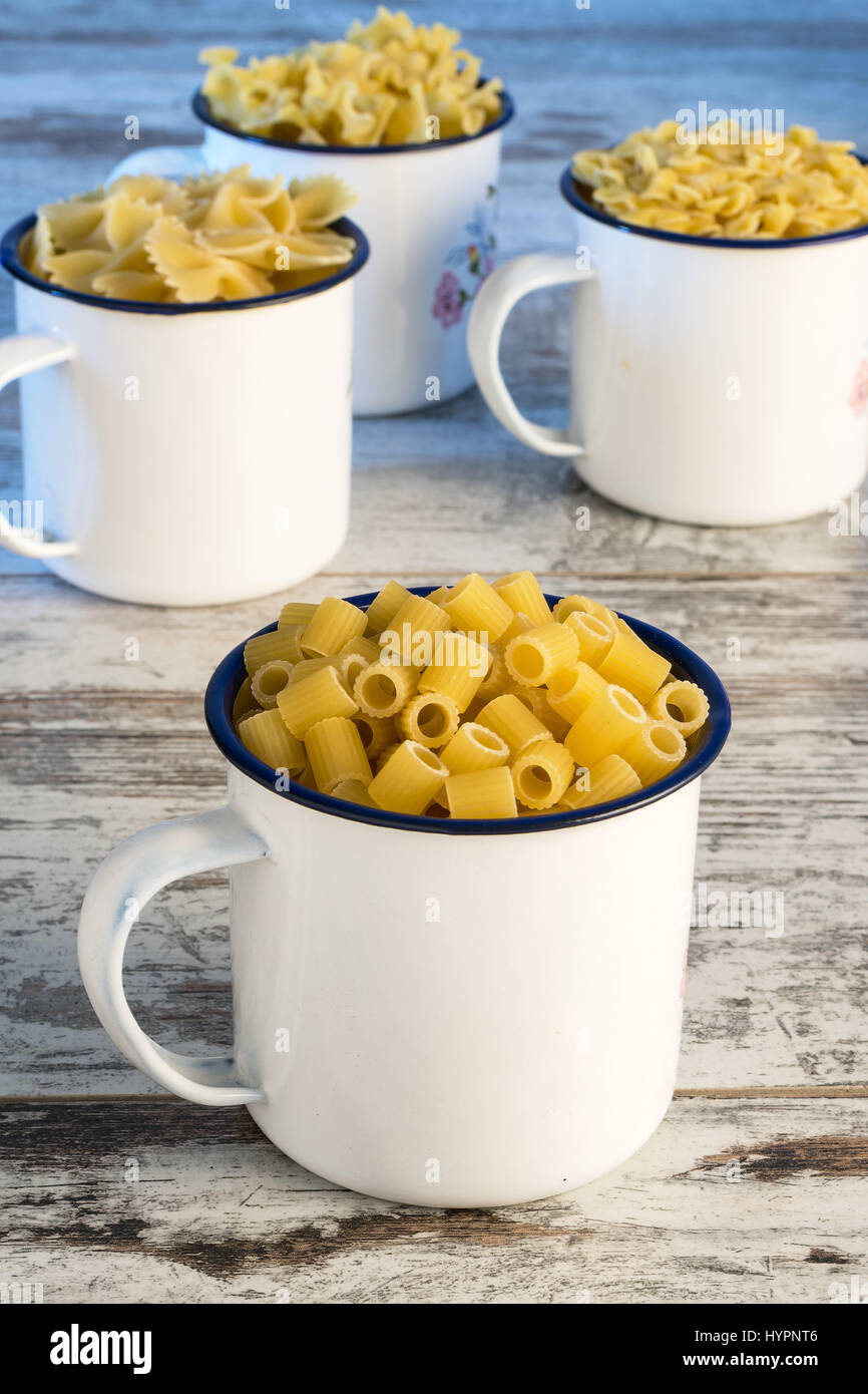 dried pasta in cup metallic fingering front - Stock Image