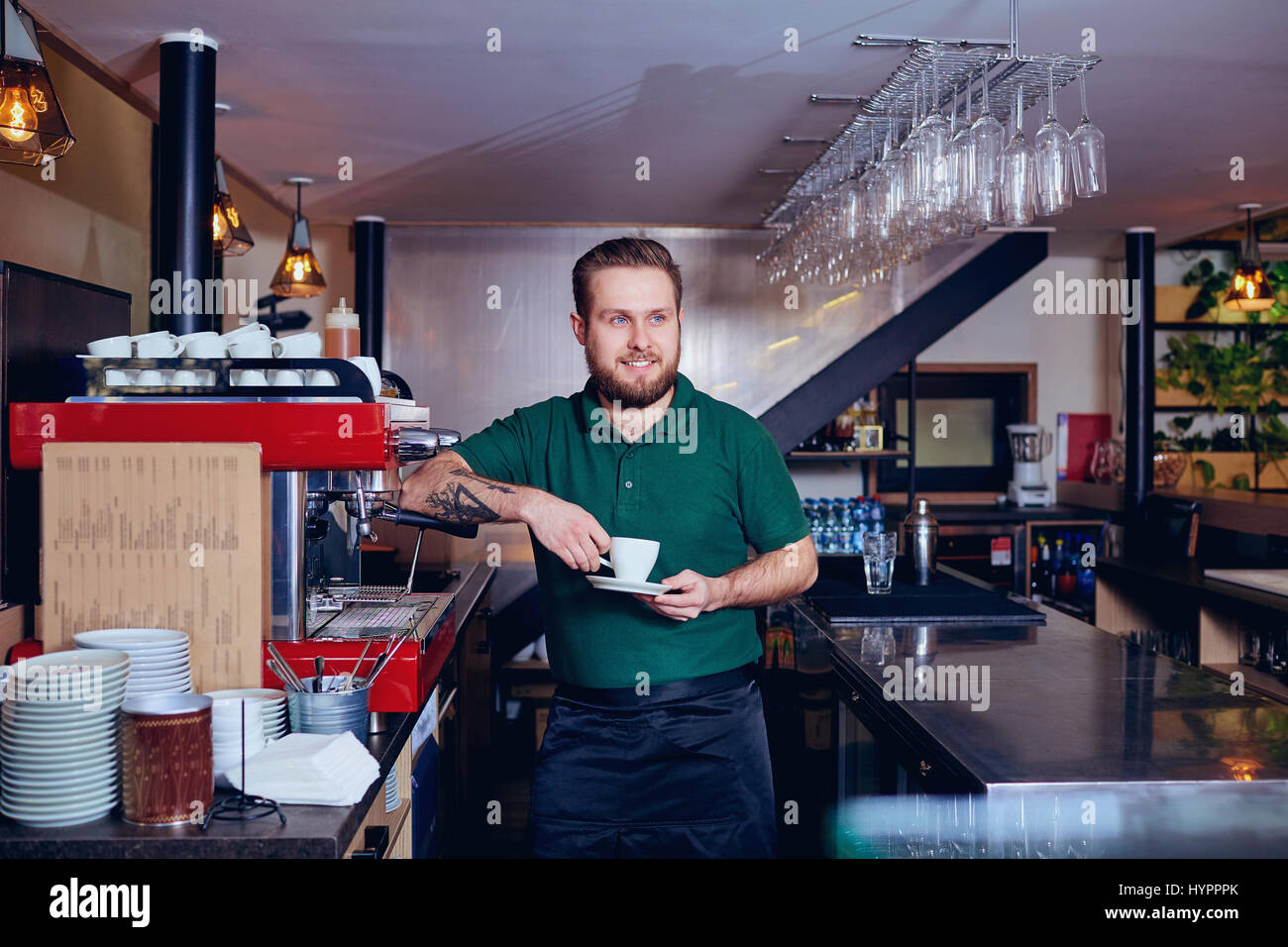 Bartender barista with coffee in hand behind the bar - Stock Image