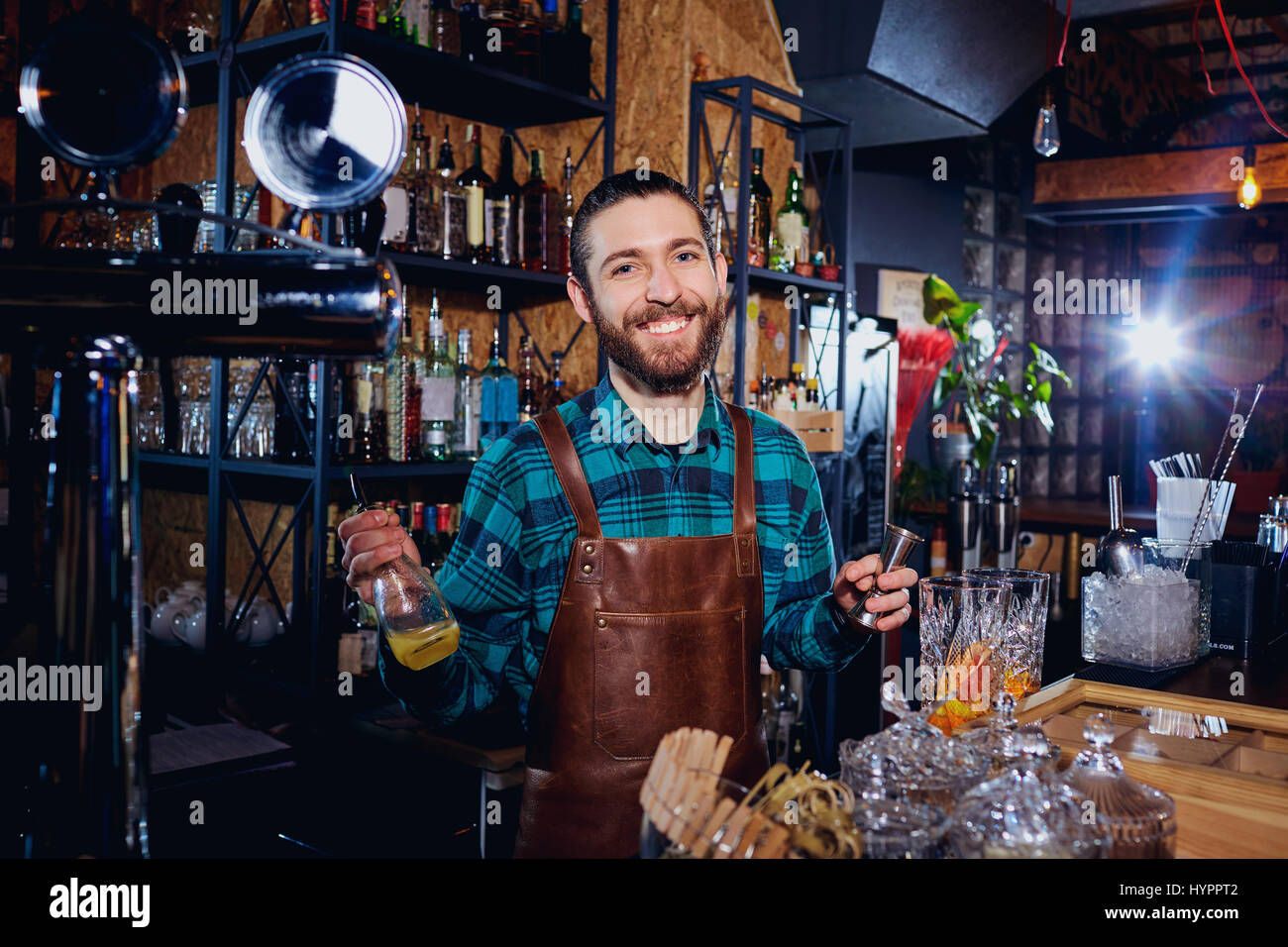 The bartender laughs making a cocktail at the bar - Stock Image