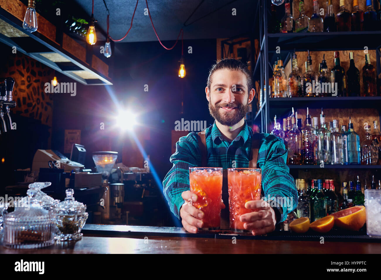 Barman holds out cocktails to  client at the bar in restaurant.  - Stock Image