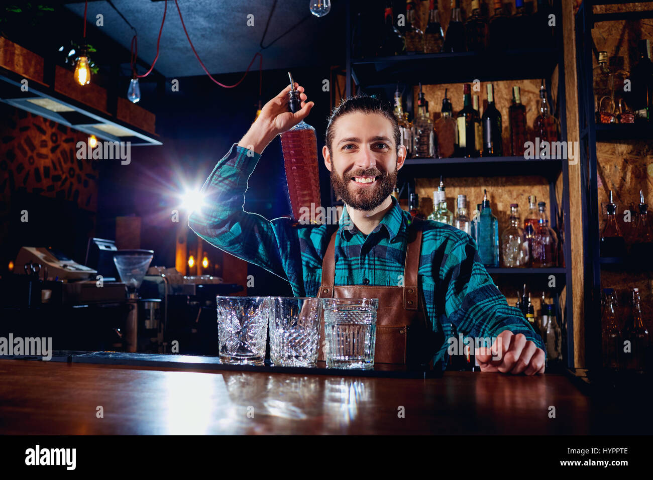 A barman with bottle of alcohol smiles laughing at the bar - Stock Image