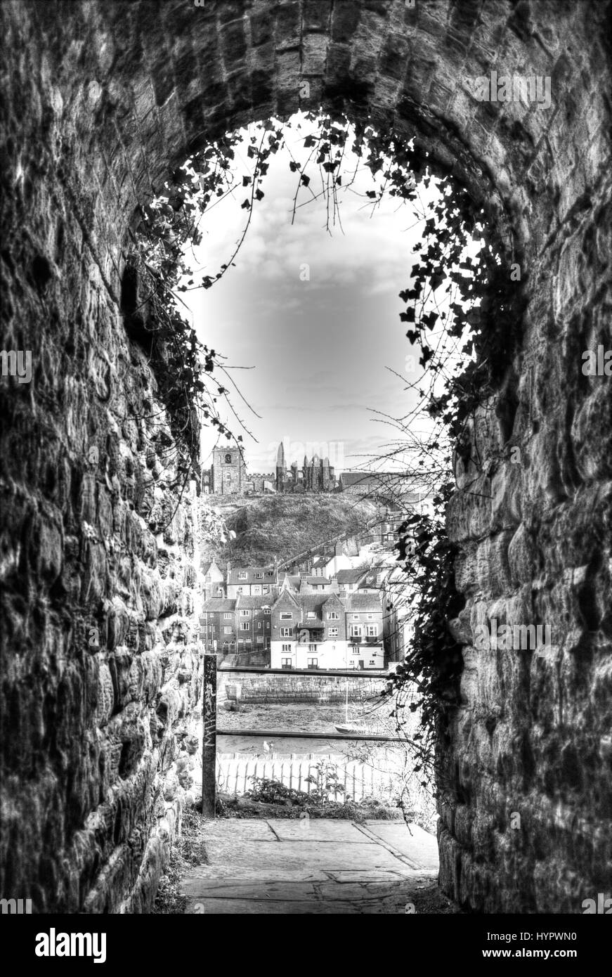 Whitby Abbey Whitby town Whitby town Yorkshire UK England framed by alley alleyway black and white dramatic print - Stock Image