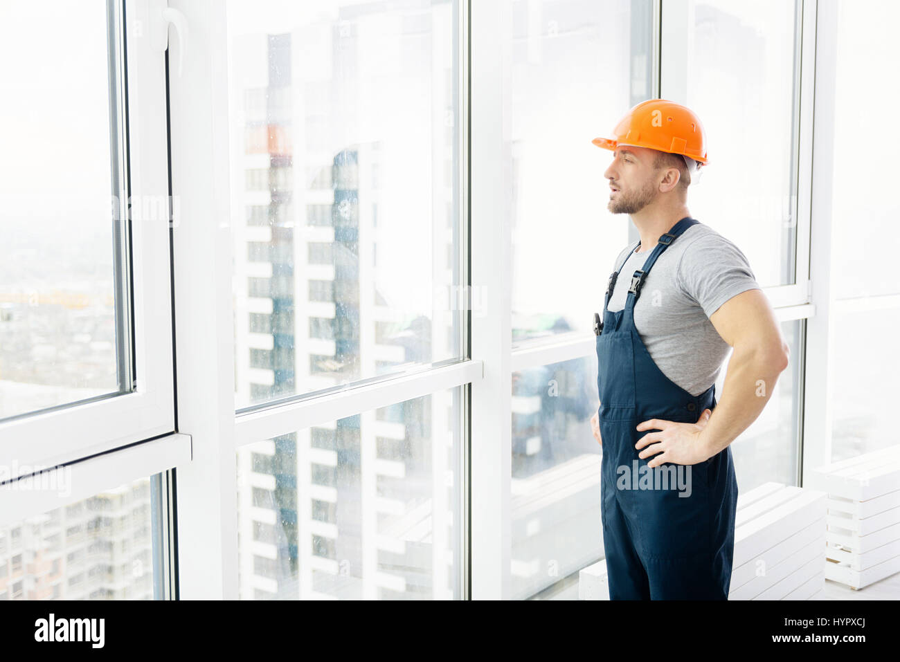 Serious construction engineer standing near window - Stock Image
