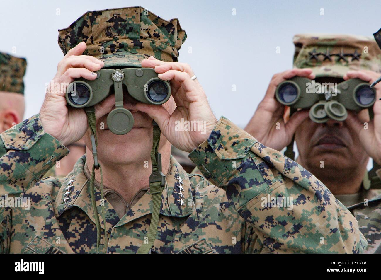 U.S. Marine Corps Commandant Gen. Robert Neller, left, and  Army Gen. Vincent Brooks, U.S. and U.N. Forces Korea commander, watches an amphibious assault demonstration with binoculars during at the annual PALS 2017 exercises April 2, 2017 in Pohang, South Korea. PALS is held annually to help strengthen relationships between Indo-Asia-Pacific region Marine and Naval forces. Stock Photo