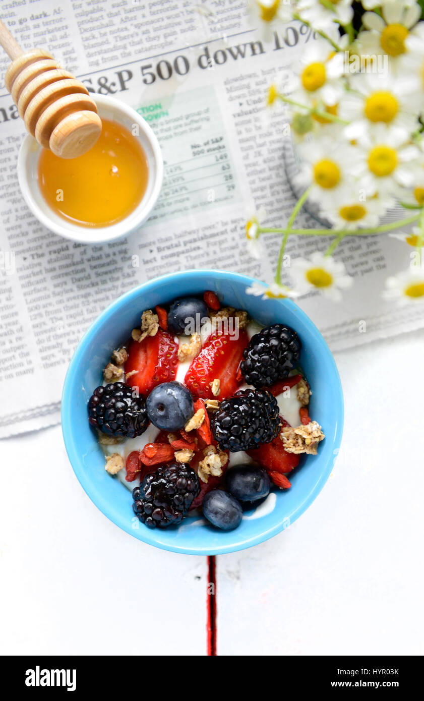 Strawberries and blueberries in bowl of yogurt on table with honey, newspaper and daisies Stock Photo