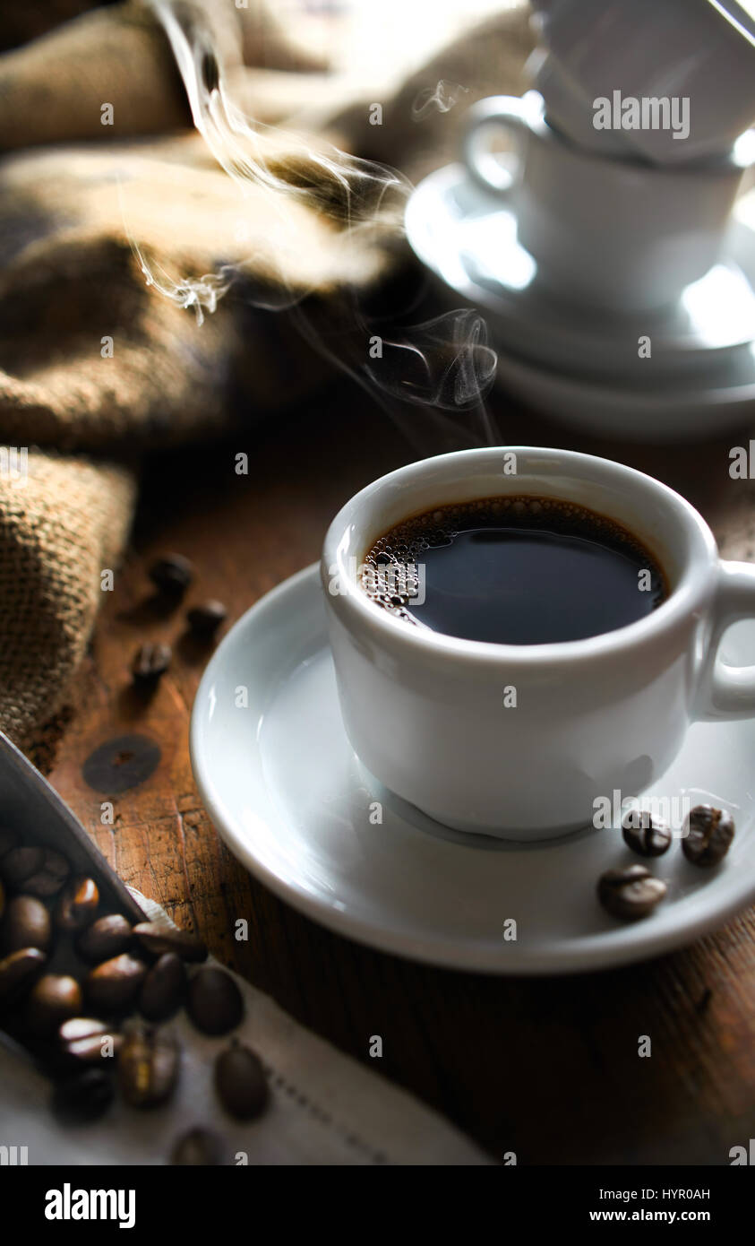 Cup of espresso steaming with coffee beans in foreground and mugs in background. Stock Photo