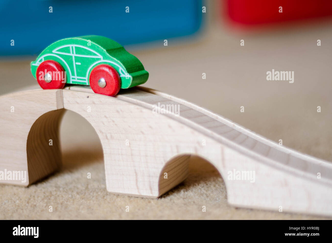 A toy wooden car on top of a toy wooden bridge. The car runs a long a track with grooves to guide it's wheels. - Stock Image