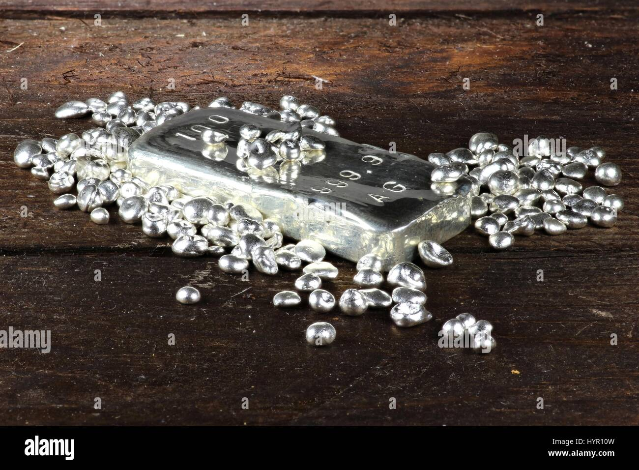 silver ingot and granules on wooden background - Stock Image
