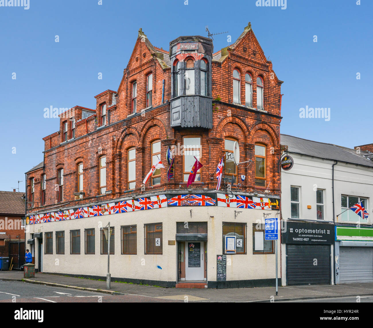 Brick house with UK flags near Shankill Road in Belfast, Northern Ireland - Stock Image