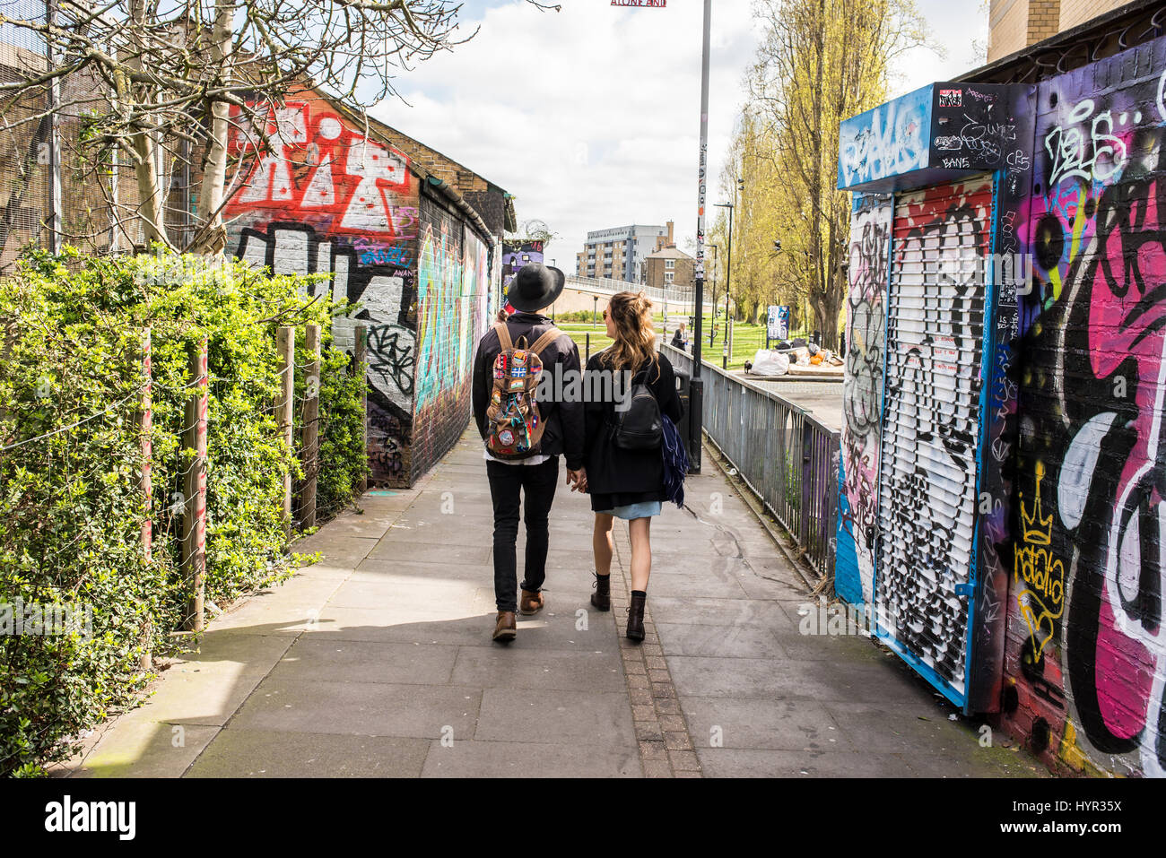 Hipster couple from behind walking in Brick Lane, Shoreditch, London, UK. - Stock Image