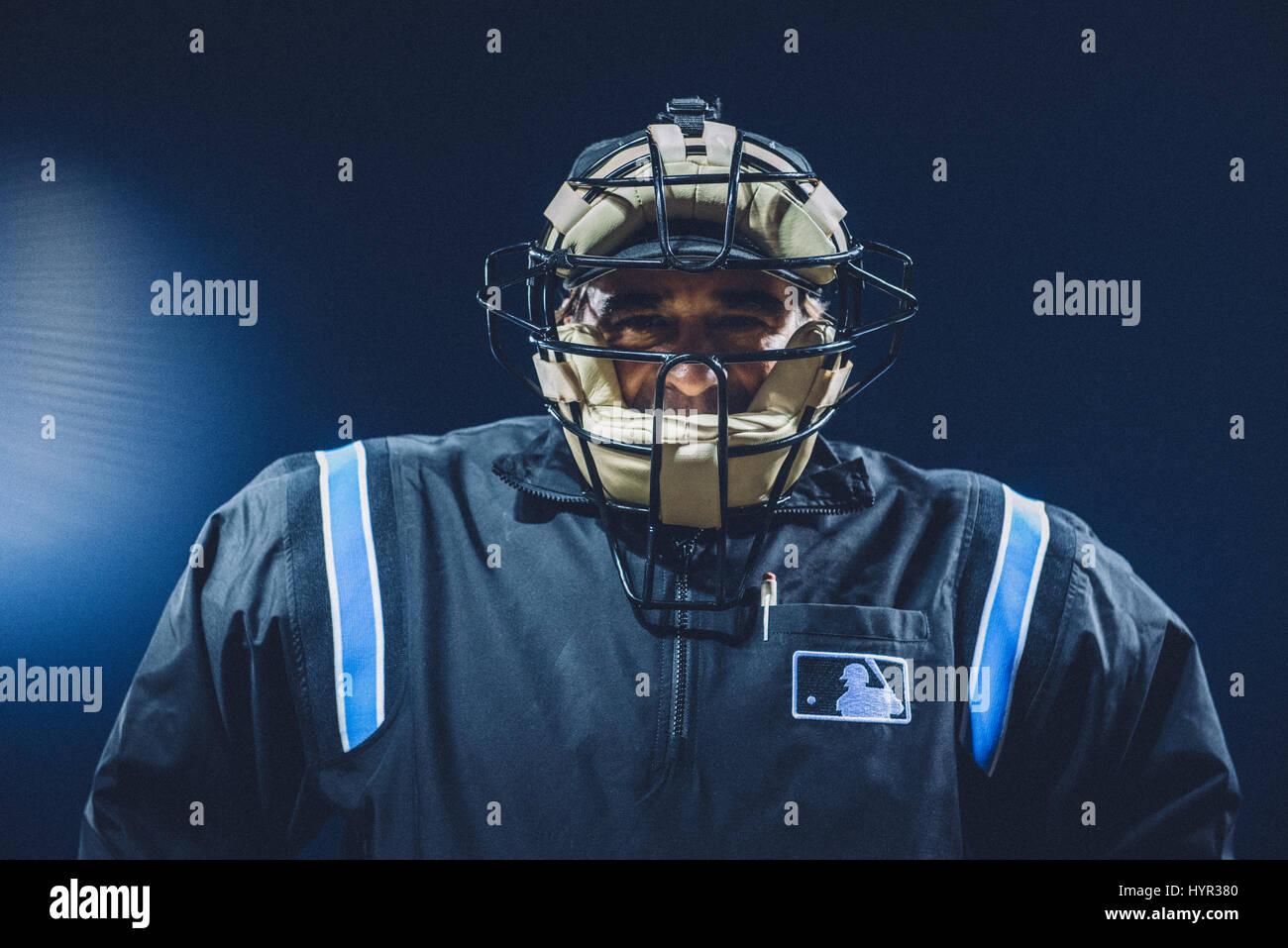 Baseball umpire looking down at camera with an imposing, menacing glare. - Stock Image