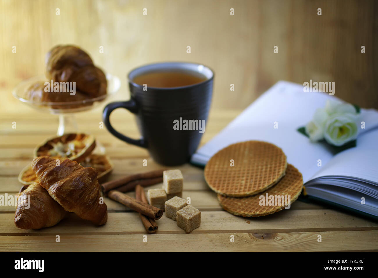 cup with tea croissant book Stock Photo