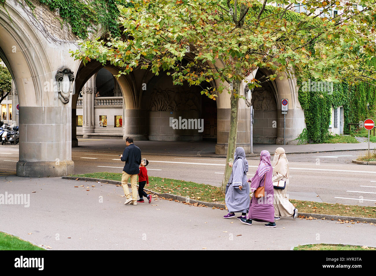 Traditional muslim family with husband and a child and three women in hijabs in the streets of Zurich, Switzerland - Stock Image