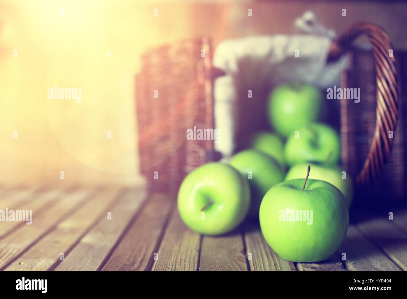sunlight green apple in a basket wooden background - Stock Image