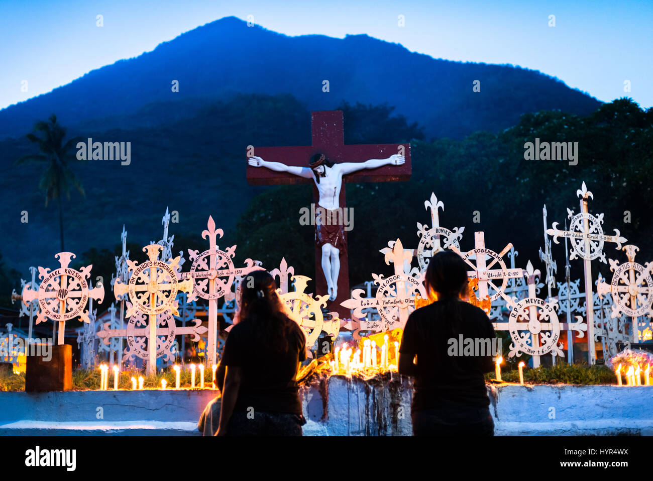 Two women pray at the Cathedral Cemetery as a part of Holy Week celebration in Larantuka, Indonesia. - Stock Image