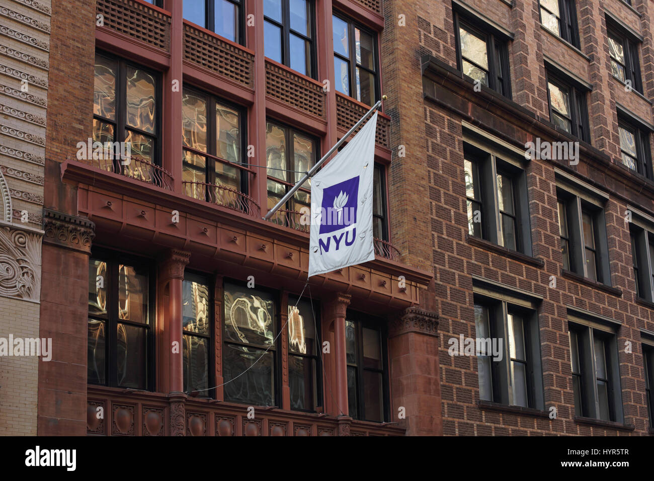 New York, NY, USA - February 6, 2017: A New York University banner hangs from a flagpole outside college buildings - Stock Image