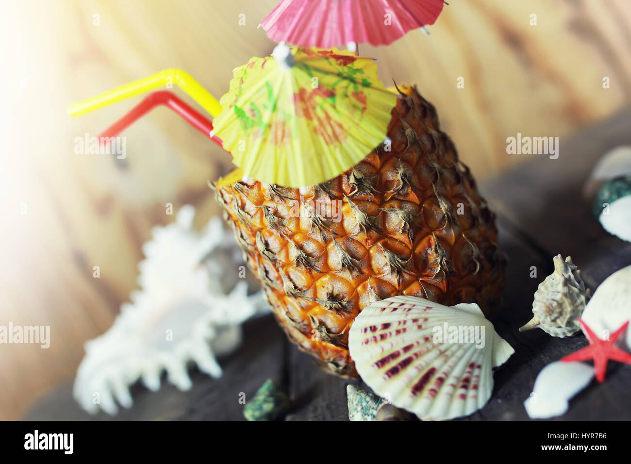 pineapple with straw and cocktail umbrella - Stock Image