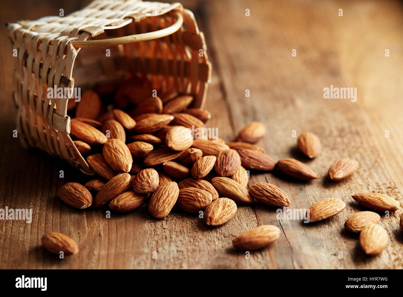 Whole almonds falling out of a small basket. A pile of almonds on a wooden surface. - Stock Image