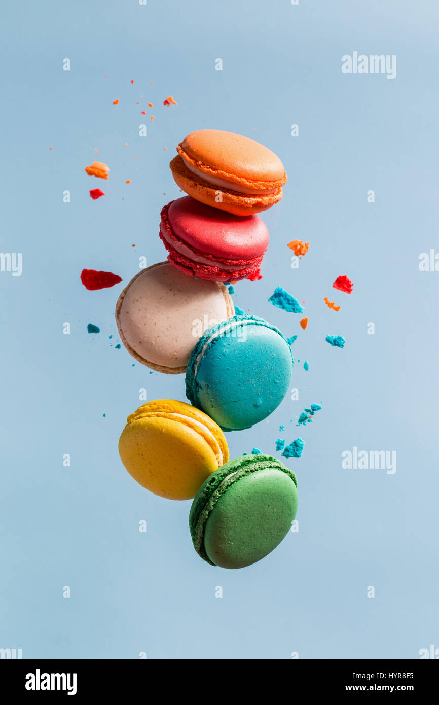 Different types of macaroons in motion falling on blue background. Sweet and colourful french macaroons falling - Stock Image