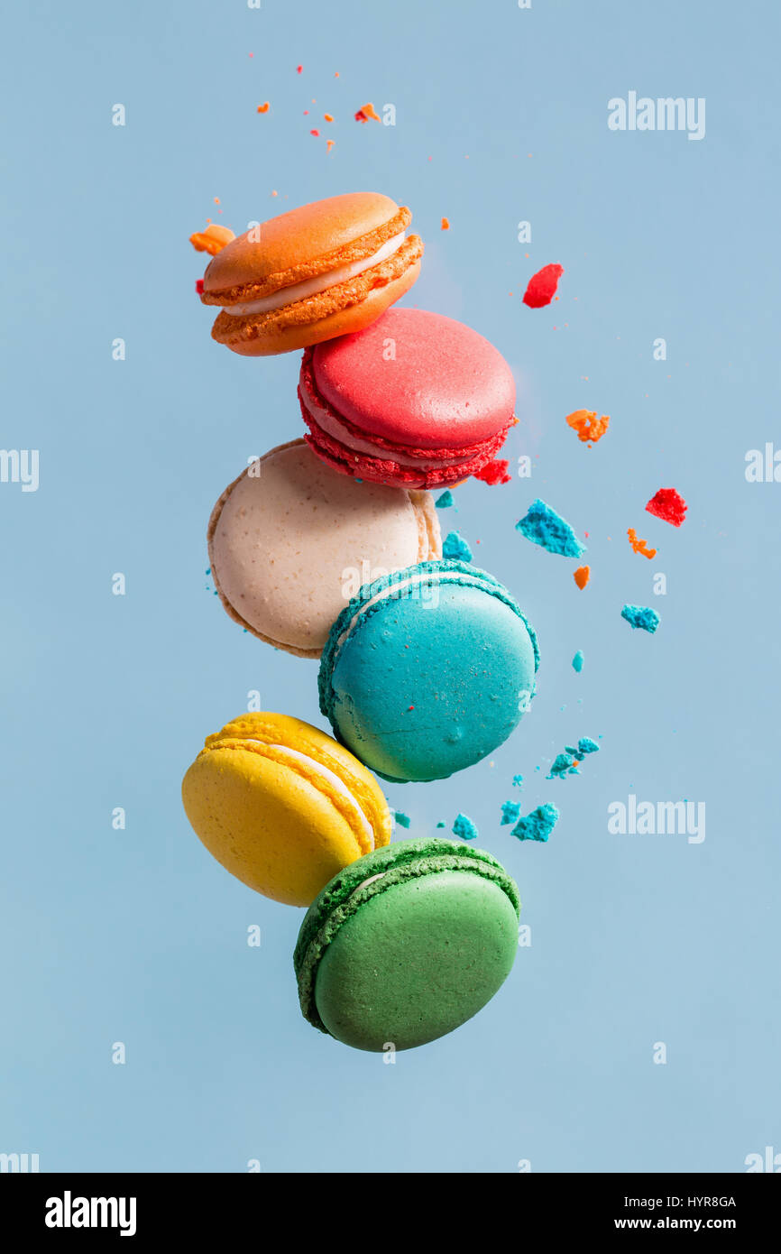 Different types of macaroons in motion falling on light  blue background. Sweet and colourful french macaroons falling - Stock Image