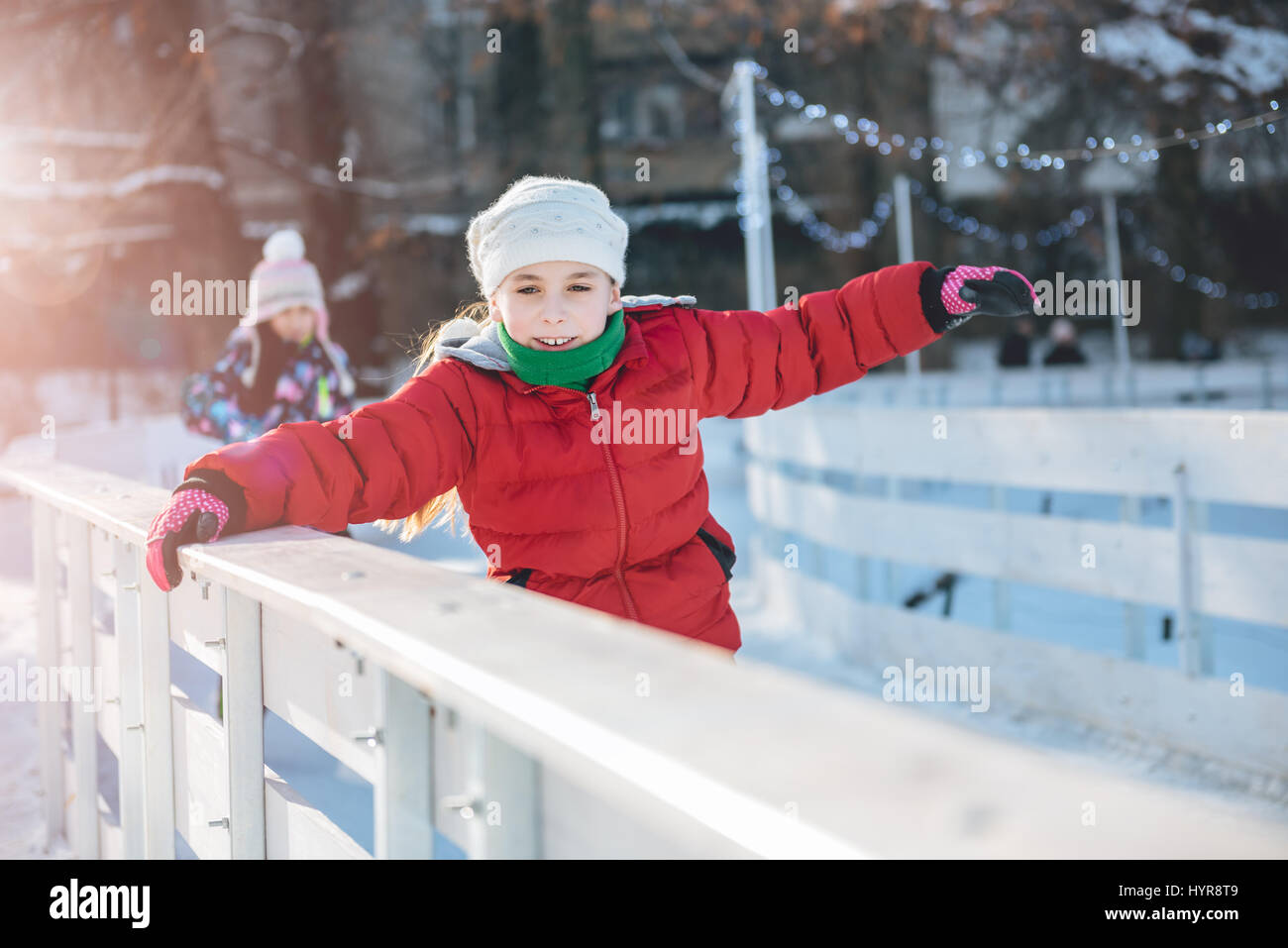 Two girls learning to skate on the temporary ice rink - Stock Image