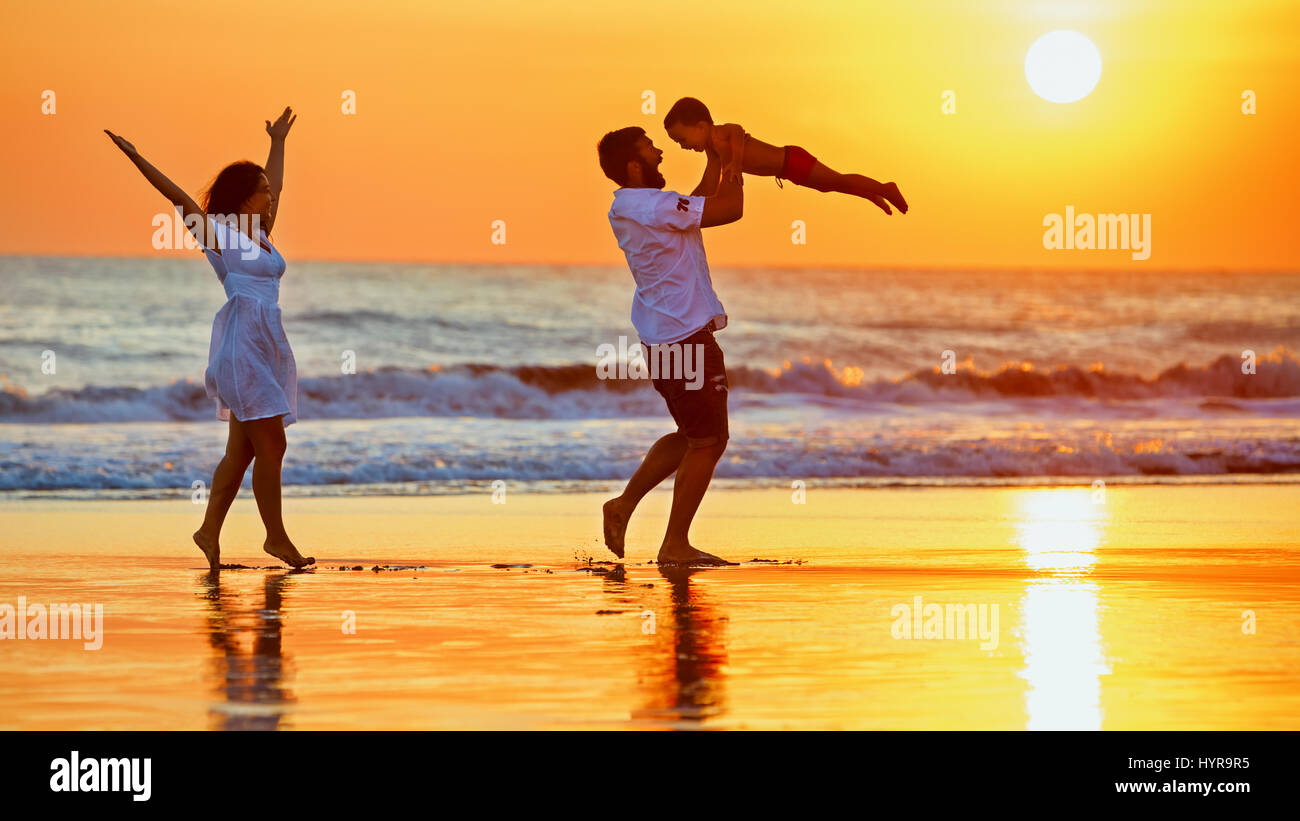Happy family - father, mother, baby son walk with fun along edge of sunset sea surf on black sand beach. Active - Stock Image