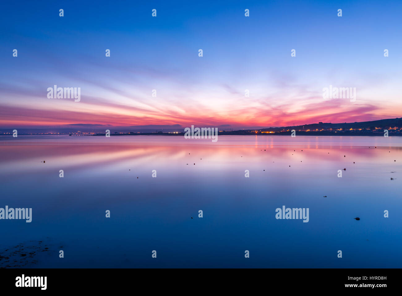 As the sun rises over Instow, the dramatic rays of sunllight reflect in the still waters of the the estuary, where - Stock Image