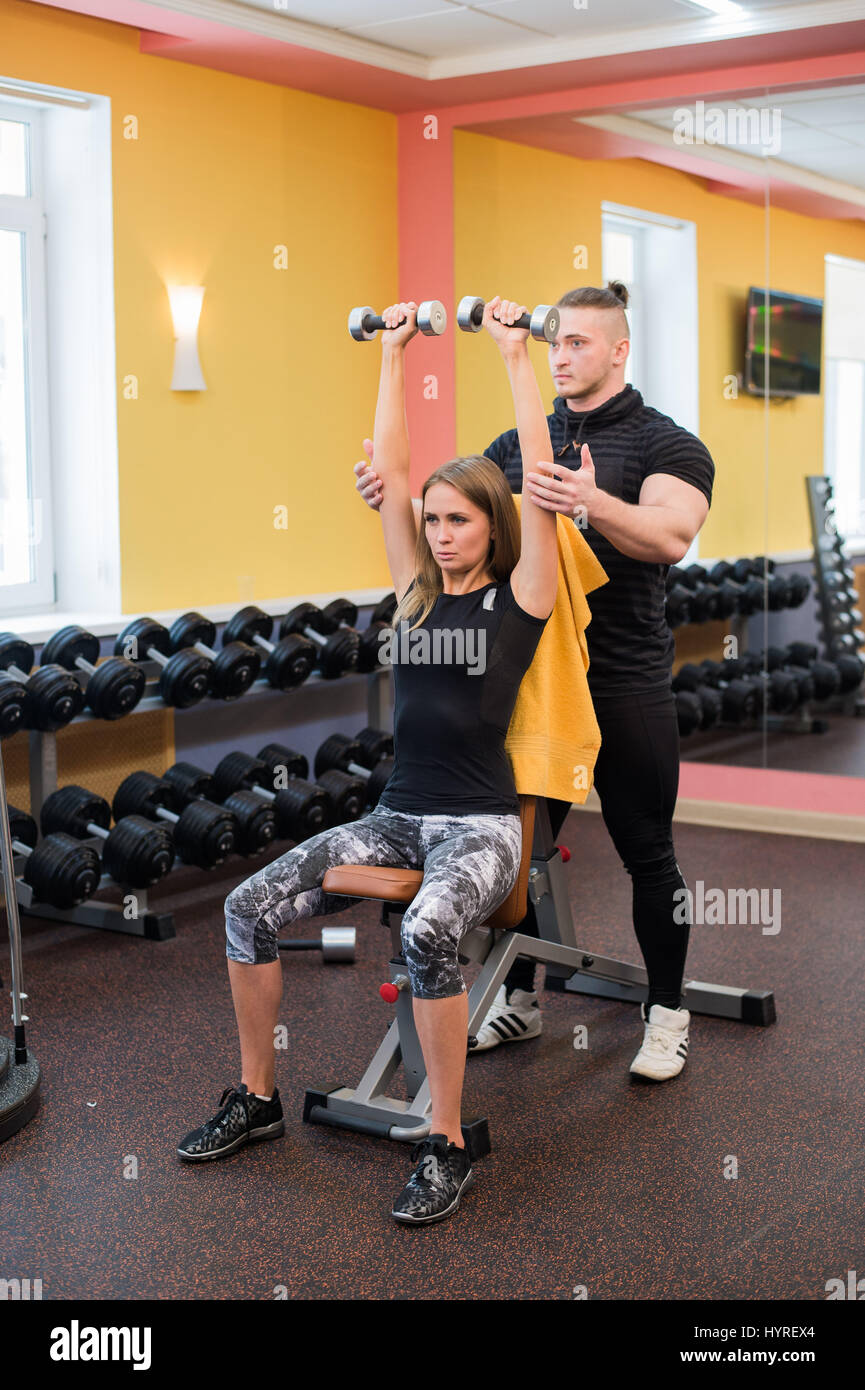 Woman with her personal fitness trainer in the gym exercising power gymnastics with a barbell - Stock Image